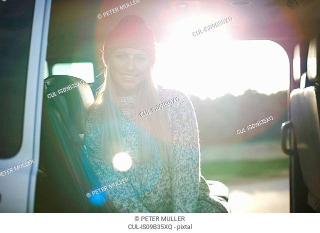 Sunlit portrait of young woman sitting in back of car