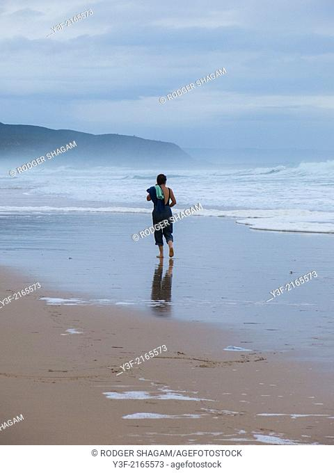 The lone figure of a woman walking along the beach at low tide. Her imager mirrored in ther shiny mud