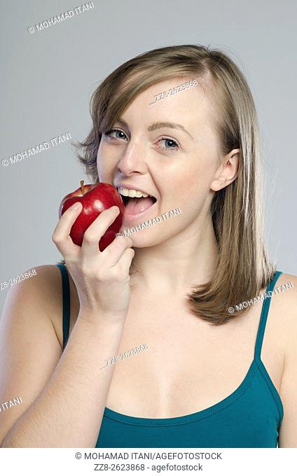 Happy young woman eating a red apple