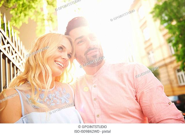 Portrait of couple in sunlight looking away smiling