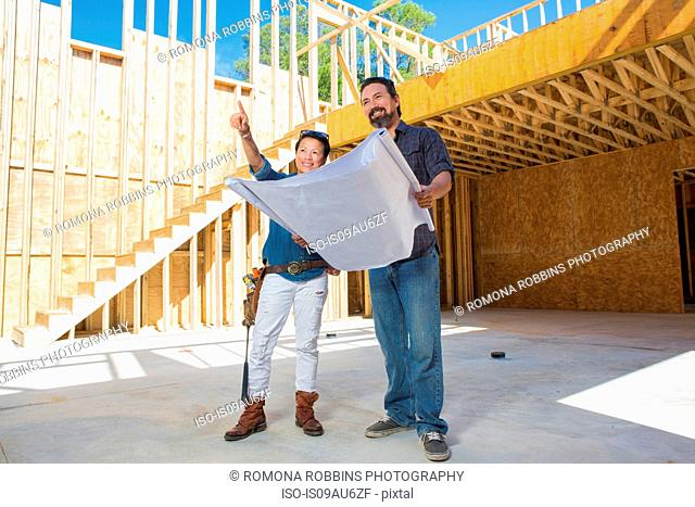 Mid adult woman discussing floor plans with builder