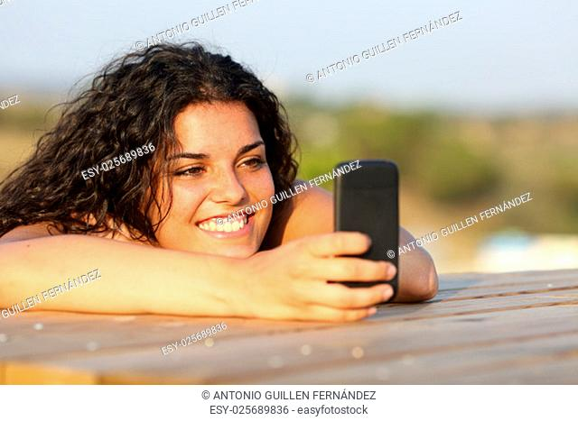 Funny girl watching social media in smart phone relaxing in a park