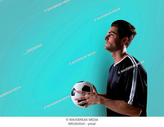 soccer player looking up with ball on hands. blue background
