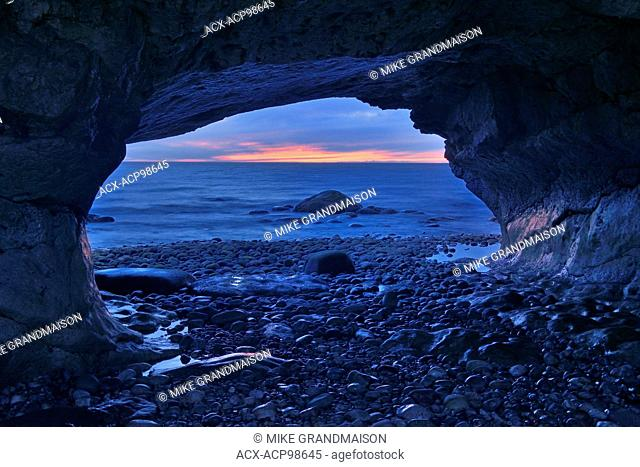Sunset on Gulf of St. Lawrence and ancient limestone carved by eons of pounding surf The Arches Provincial Park Newfoundland & Labrador Canada