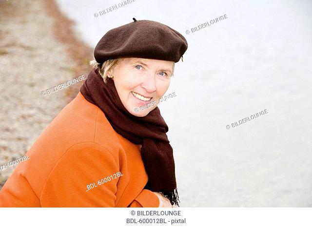 headshot of mature woman wearing brown beret standing at lake in park