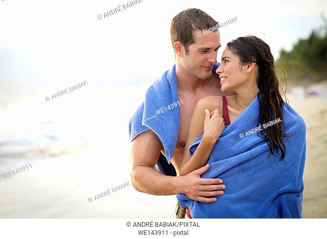 Young couple sharing a towel at a beach at Riviera Nayarit, Mexico