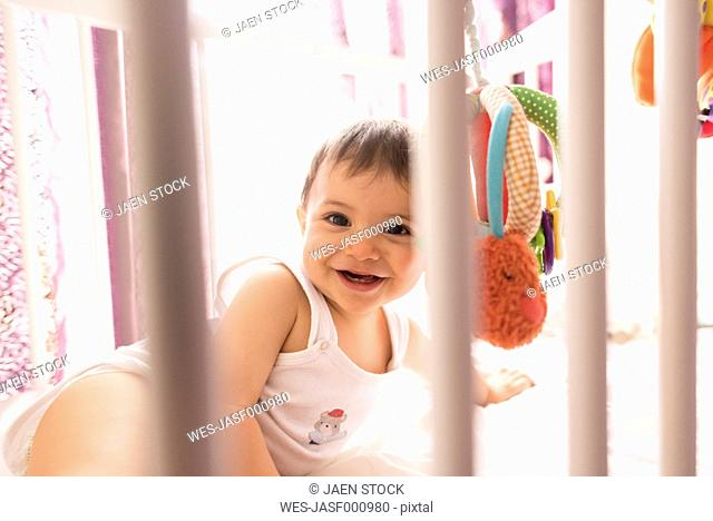 Portrait of happy baby boy in his cot