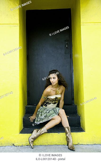 A young woman sitting in a door way