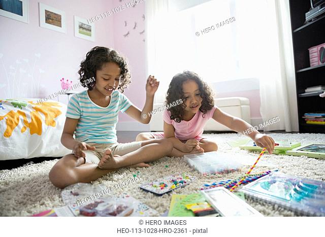 Sisters playing together on floor in bedroom