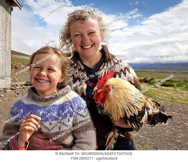 Mother and daughter with a chicken on a Goat farm, Western Iceland