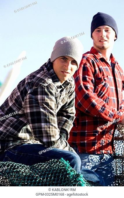 Young fishermen in plaid shirts on fishing boat