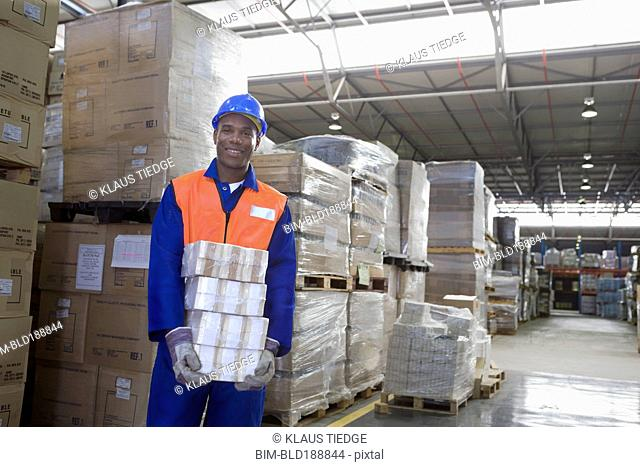 African worker carrying package in warehouse