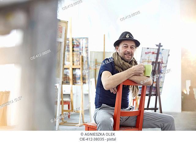 Portrait smiling, confident male artist drinking coffee in art class studio