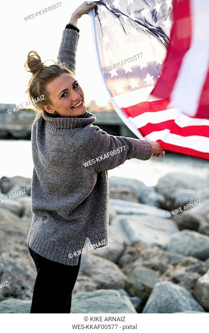 Portrait of smiling young woman holding blowing US American flag