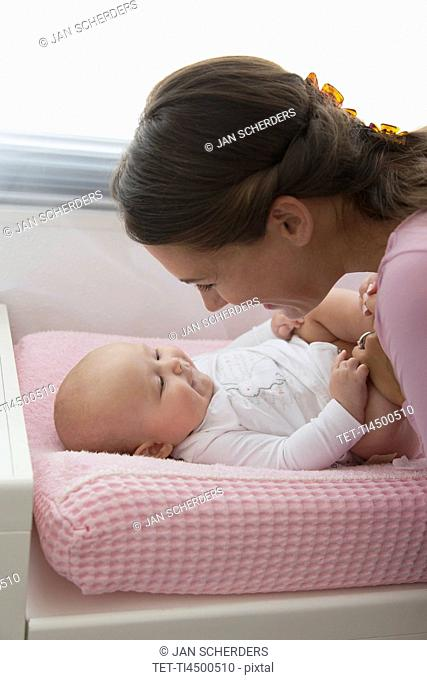 Mother playing with baby daughter 6-11 months