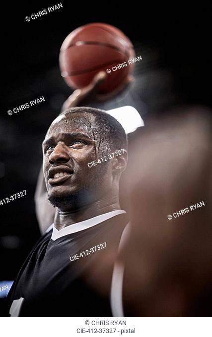 Serious, sweating basketball player holding basketball overhead