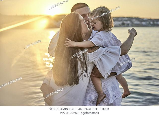 family, parenthood, sunset, candid, unposed, real people. In holiday destination Chersonissos, Crete, Greece
