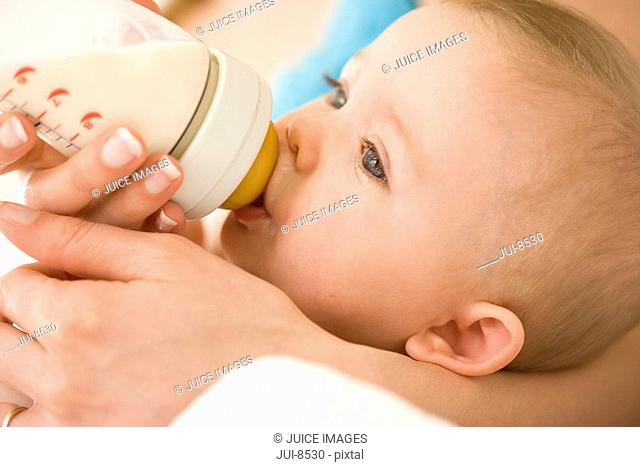 Mother feeding baby girl 9-12 months milk bottle, close-up