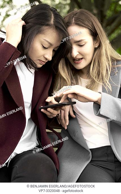 two women checking together news on smartphone, in Frankfurt am Main, Germany