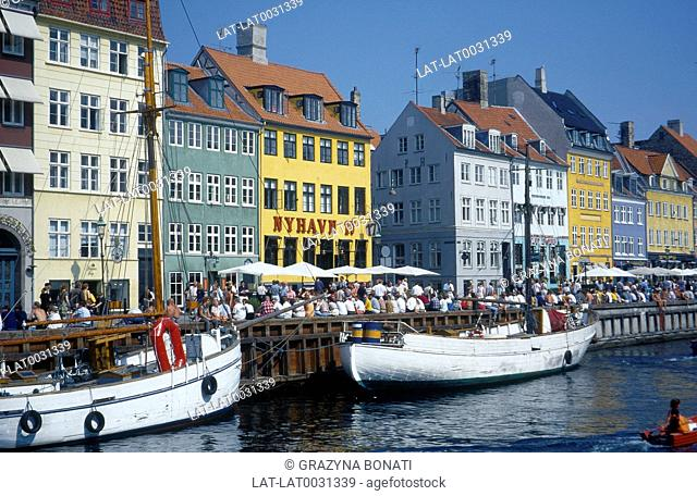 Nyhavn. People sitting on harbour wall. Boats. Buildings. Restaurants / cafes