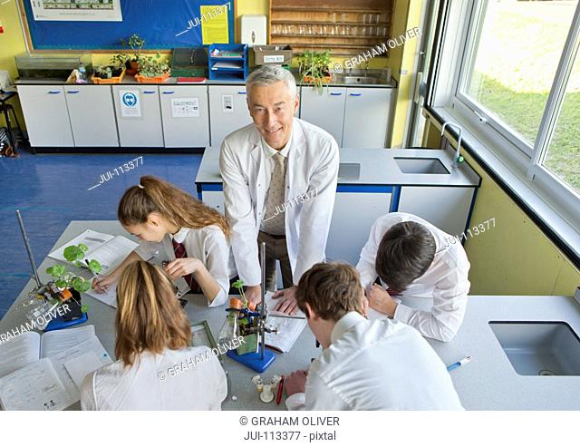 Portrait smiling biology teacher with high school students conducting scientific experiment