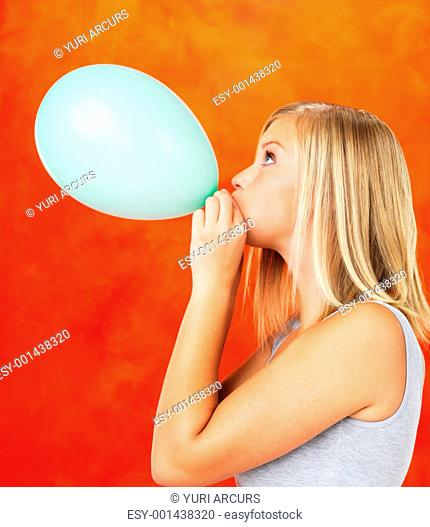 Side view of young woman blowing balloon on orange background