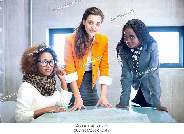 Three young women at desk with blueprint