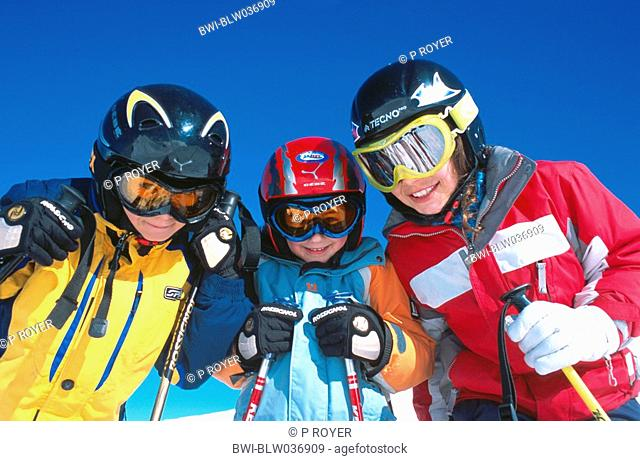 three boys skiing, wearing snow goggles and helmets