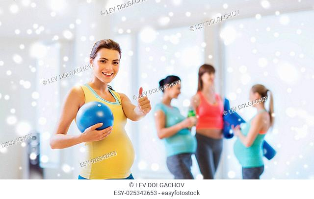 pregnancy, sport, fitness, people and healthy lifestyle concept - happy pregnant woman with ball in gym showing thumbs up over snow