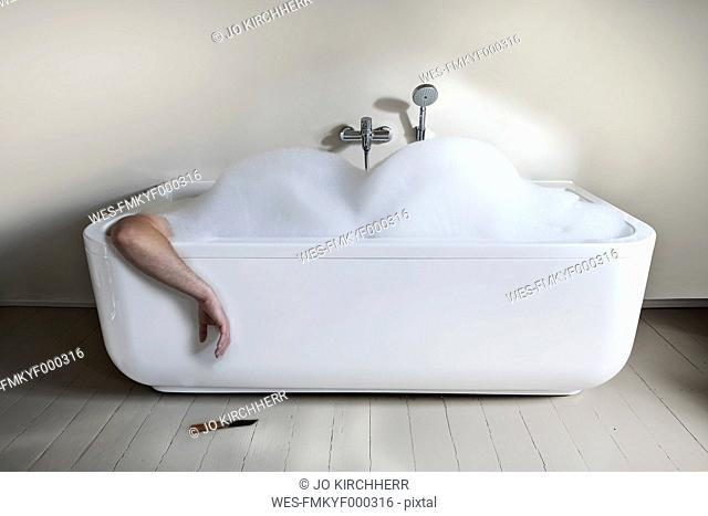 Mid adult man in bathtub with knife