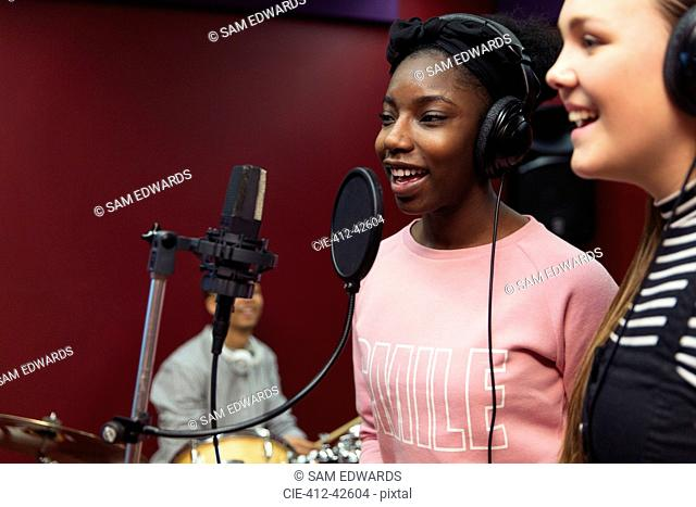 Teenage musicians recording music, singing in sound booth
