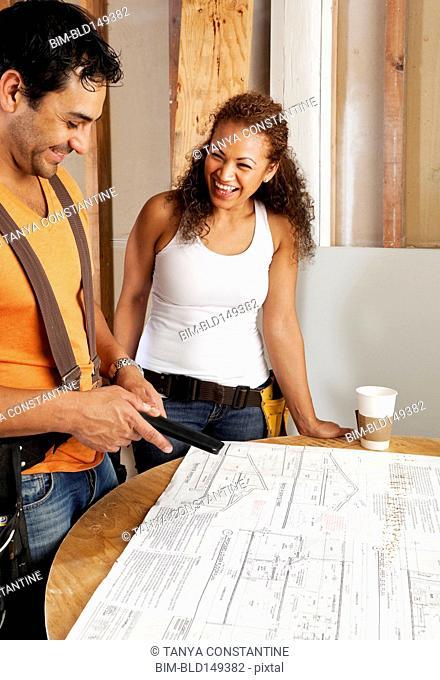 Hispanic couple looking at blueprints