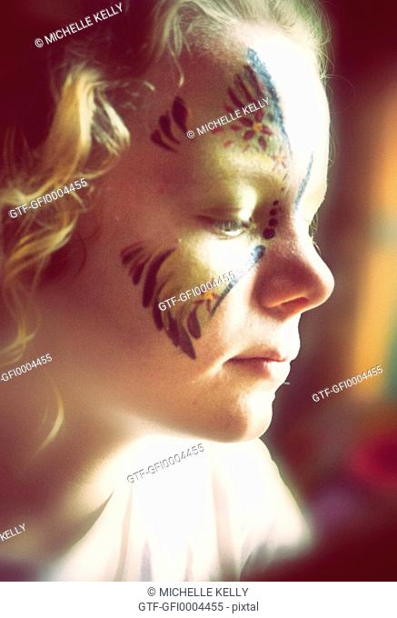 Profile of Beautiful Child with Facepaint Gazing Up out of Frame