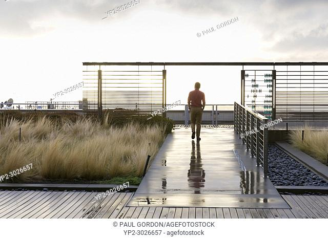 Seattle, Washington: Man walk laps on the Russell Investment Center Observation Deck as a rainstorm passes. The 25,000 square foot terrace on the buildings 17th...