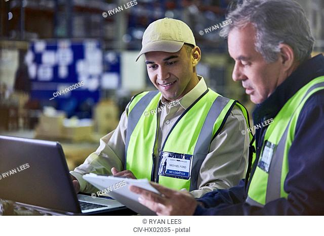 Workers with clipboard and laptop working in distribution warehouse