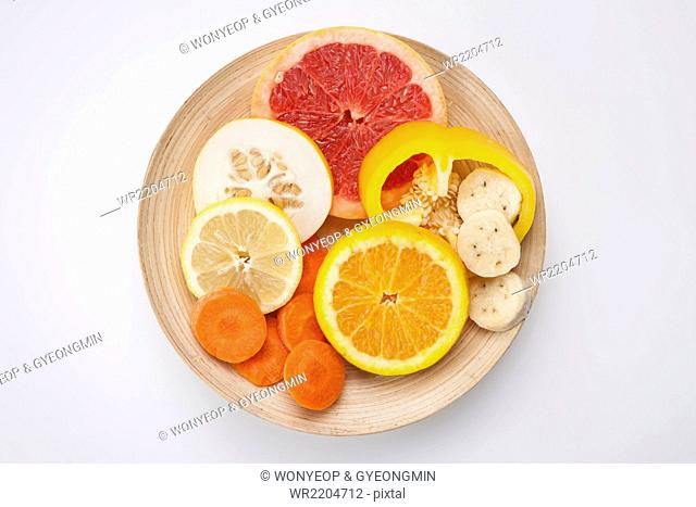 High angle of slices of yellow and orange color of fruits and vegetables such as grapefruit, oriental melon, lemon, orange, banana, carrot
