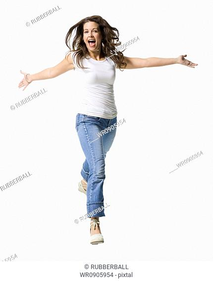 Portrait of a mid adult woman running with her arms outstretched