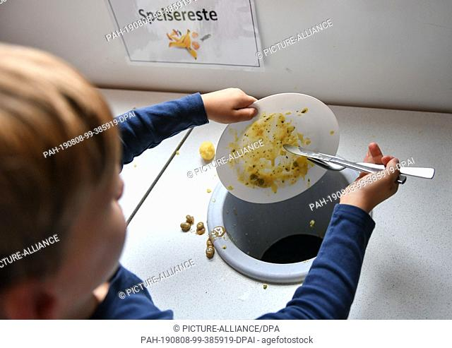 07 August 2019, Berlin: After lunch, a student throws food scraps into containers provided. Photo: Jens Kalaene/dpa-Zentralbild/ZB