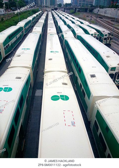 Several Go Trains resting with city in the distance. Toronto, Ontario, Canada