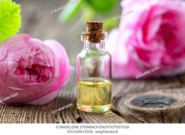 A bottle of essential oil with fresh cabbage roses on a table