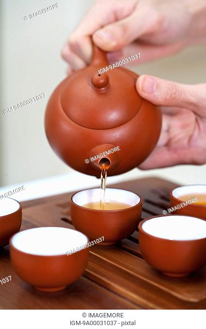 Tea, Human hands holding a teapot and pouring tea into tea cups