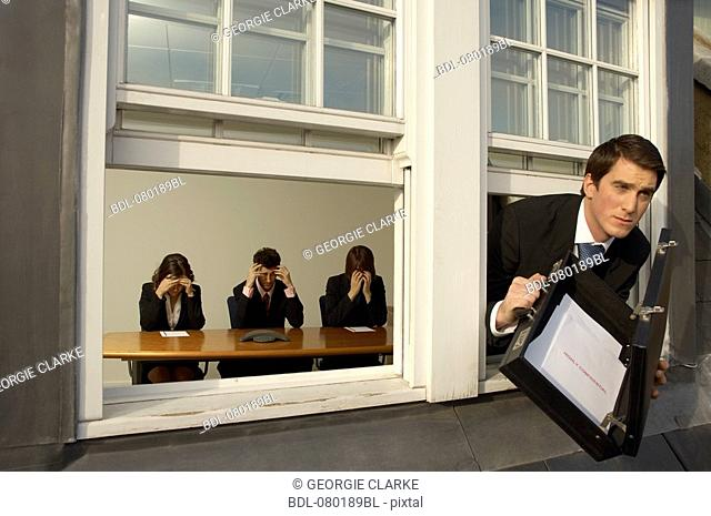 businessman leaving meeting through window with confidential documents