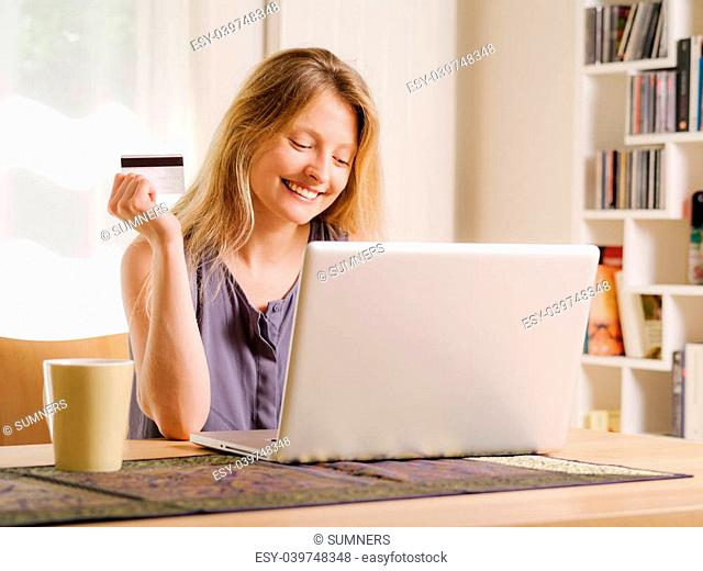 Photo of a beautiful young female shopping online and paying with a credit card. Credit card information is fictitious