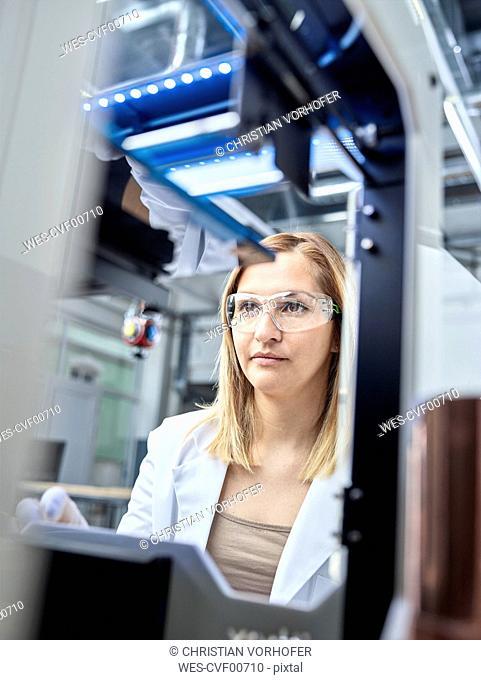 Female technician checking 3D printer