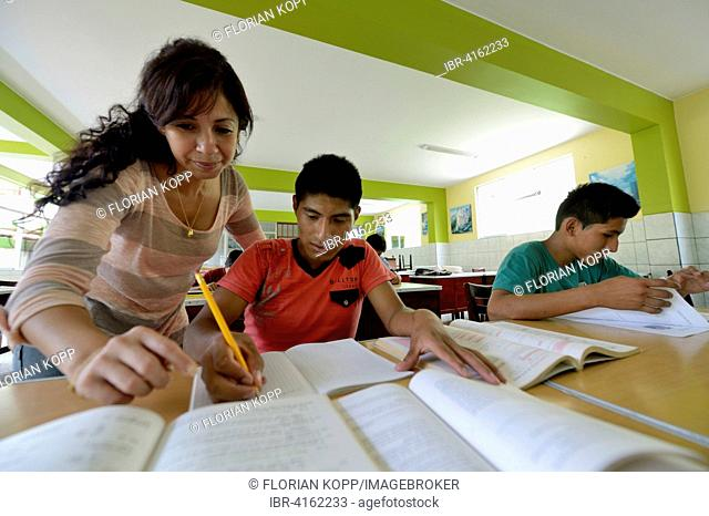 Social worker supporting a teenager, 15 years, former street child, doing homework, Brena, Lima, Peru