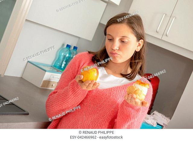 a teenage girl with sweet pastry and organic apple