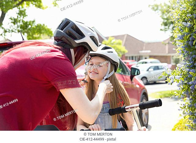 Mother fastening helmet on daughter riding scooter in sunny driveway