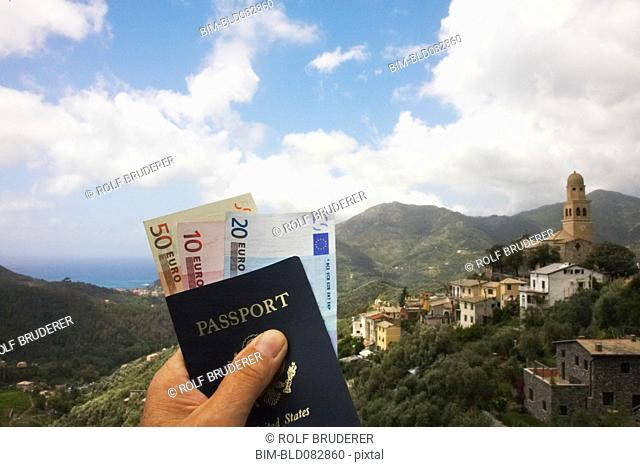 ManÆs hand holding passport and euro currency