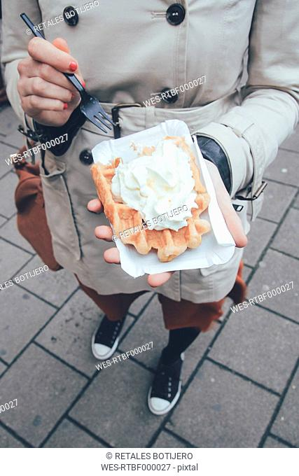 Belgium, Antwerp, young woman eating Belgian waffles on the street