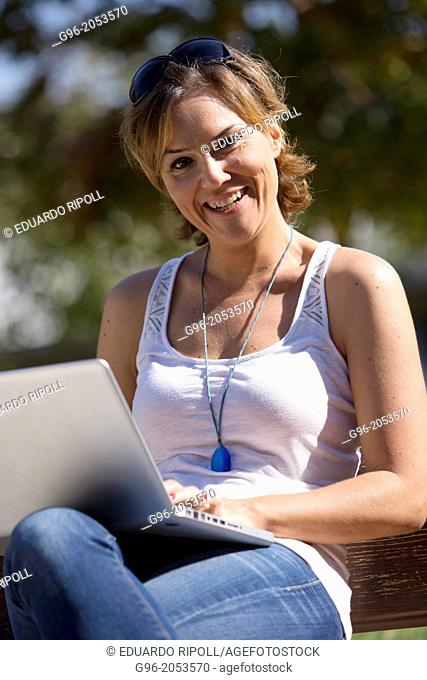 Woman with laptop in a park